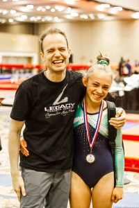 Photo of Coach Adam and a female athlete both smiling after a competition. The athlete is wearing medal around her neck.